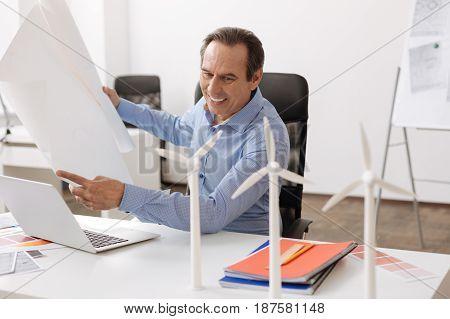 Involved in interestign project. Cheerful senior engineer sitting at the table and holding blueprint while planning construction of wind turbines