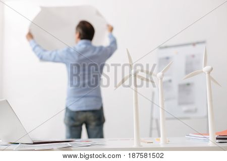 Eco tools. Selective focus of wind turbines models standing on the table while professional engineer standing in the background and holding blueprint