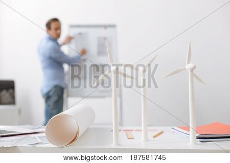 Wind power. Close up of wind turbines models standing on the table with professional engineer working in the background
