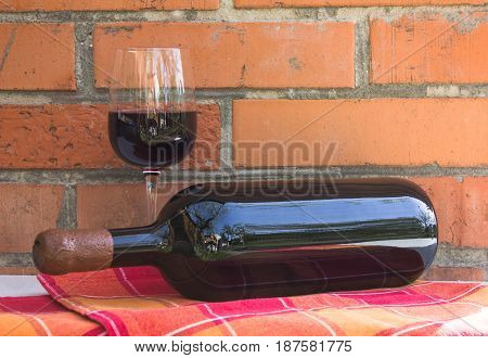 A bottle of red wine and a glass of wine on a brick wall background