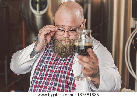Be responsible. Portrait of concentrated man tasting ale at brewery. He standing with dark beer while touching his eyeglasses. Focus on face of worker