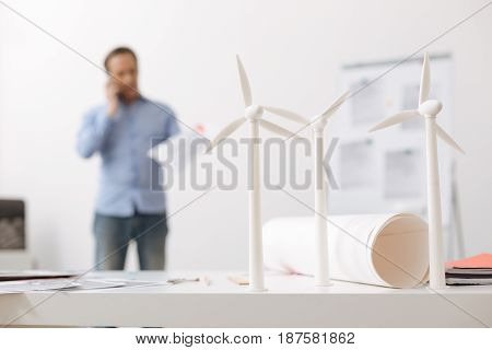 Future wind farm. Close up of wind turbines models standing on the table while professional engineer talking on cell phone in the background