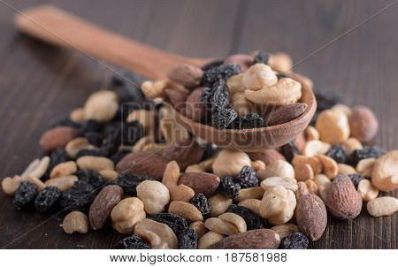Dried fruits with nuts in a wooden spoon. Wooden background
