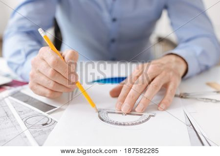 Pay attention to accuracy. Professional enginner sitting at the table and using a protractor while drawing a scheme