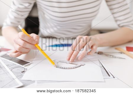 Crafty fingers. Skillful professional female enginner using protractor and working on the project while sitting at the table