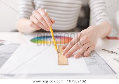 Make it straight. Close up of a ruler in hands of professional skillful female engineer drawing and working on the project in the office