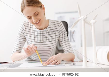 Enjoy what you do. Positive beautiful female engineer sitting at the table and making a drawing while working on the project
