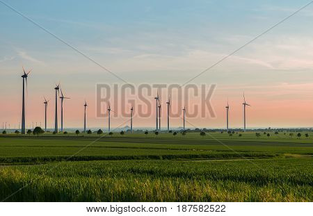 Wind generators produce environmentally friendly energy, a beautiful summer evening