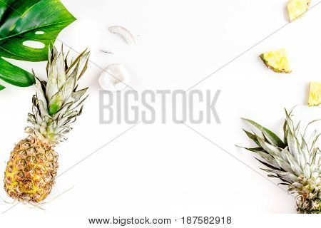 summer dessert with pineapples and leaves on white table background top view mock up