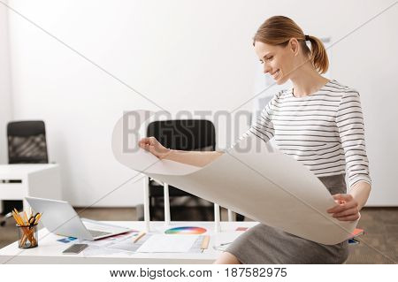 How make it real. Positive professional female engineer sitting in the office and holding blueprint while smiling