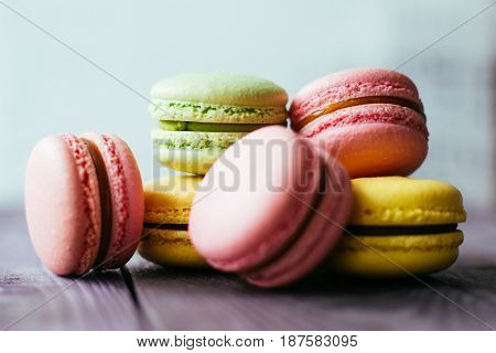 Fresh baked colored macaroon pastry cookies macarons, macaroni on a white plate close up, low angle view.