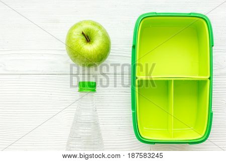 green lunchbox and bottle of water for healthy food dinner at school on white wooden table background top view