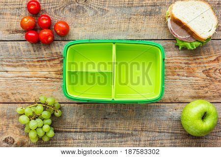 homemade lunch with apple, grape and sandwich in green lunchbox on wooden table background top view