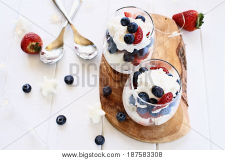 Trifles made with blueberries strawberries whipped cream and star shaped pound cake against a white wood background. Perfect for fourth of July. Shallow depth of field with selective focus.