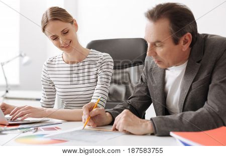 Work in cooperation. Pleasant concentrated engineer drawing and sitting at the table while working in the office with his colleague