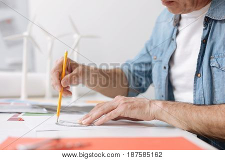 Make everything correctly. Professional skillful engineer sitting at the table and using a protractor while drawing a blueprint