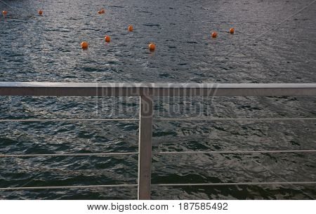 Ten pink buoys on the surface of the lake. Blurred background