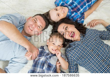 Happy family, mother, father and two sons having fun lying on the floor, upper view.