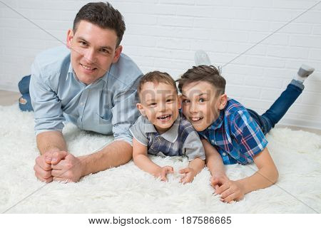 Happy family, mother, father and two sons having fun lying on the floor