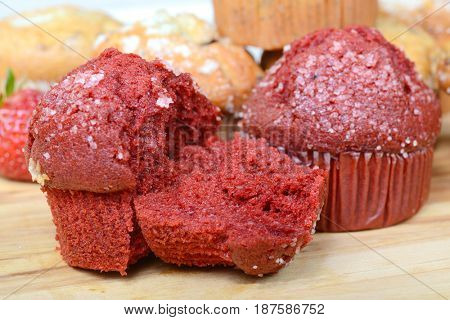 Delicious variety of muffins showcasing a Red Velvet muffin that is broken open showing the moist and flavorful inside.