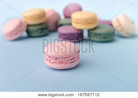 Image of a lot of sweet colorful macaroons on blue table background. Focus on purple macaroon.