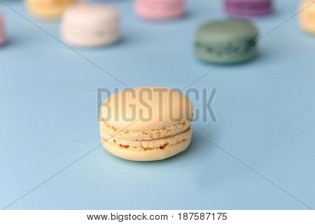 Picture of a lot of sweet colorful macaroons on blue table background. Focus on yellow macaroon.