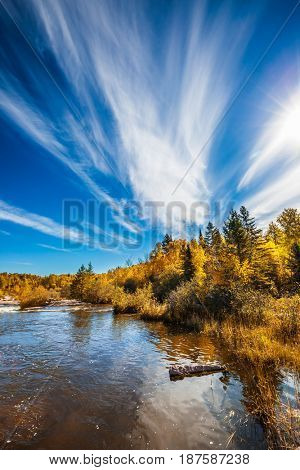 Incredible cirrus clouds over the Winnipeg River. Indian summer in Manitoba, Canada. Old Pinawa Dam Park. The concept of ecological and recreational tourism