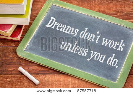Dreams do not work unless you do  - white chalk text on a slate blackboard with a stack of books against rustic wooden table