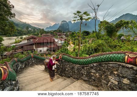 Vang Vieng, Laos - January 20, 2017: Unidentified senior woman walking up the temple stairs with beautiful rural landscape on background in Vang Voeng, Laos.