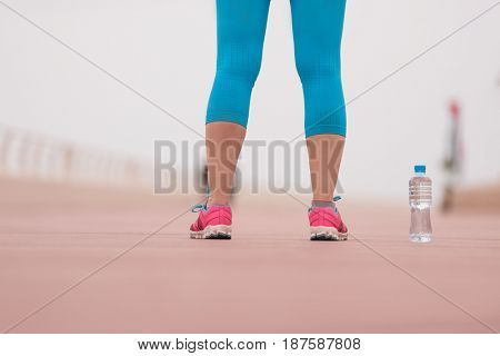 Fitness woman training and jogging in summer park, close up on running shoes and bottle of water. Healthy lifestyle and sport concept