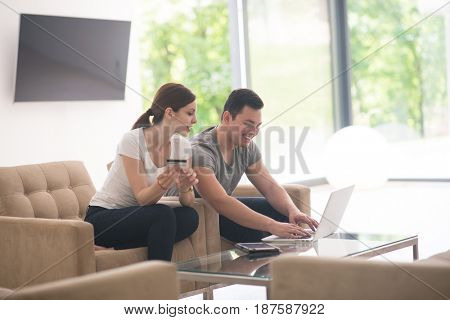 happy young couple buying online using laptop a computer and a credit card in their luxury home villa