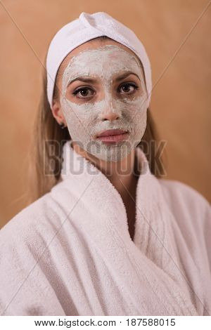 Spa Woman applying Facial Mask  Beauty Treatments  Close up portrait of beautiful girl with a towel on her head applying facial mask