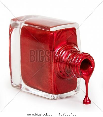 Red nail polish poured from a bottle. Isolated on white background
