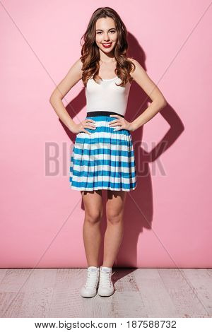 Full length portrait of a happy casual girl standing with hands on hips over pink background