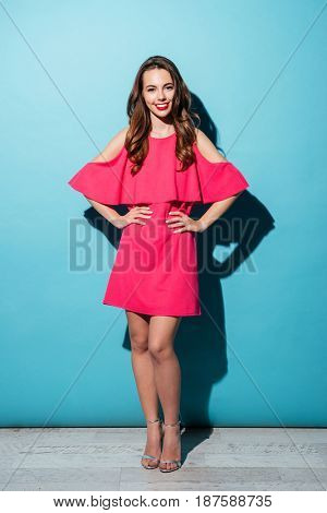 Portrait of a pretty smiling woman in dress standing with hands on hips over blue background