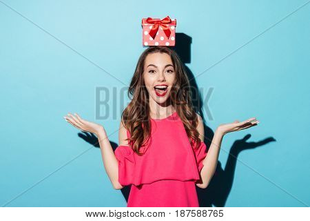Portrait of an excited brunette girl in dress with a gift box on her head isolated over blue background