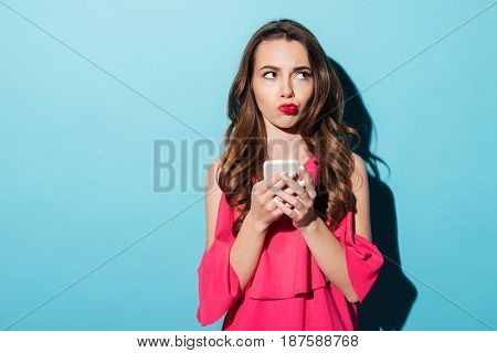 Portrait of a young confused girl in dress holding mobile phone isolated over blue background