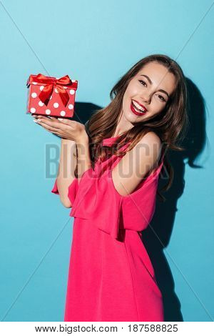 Portrait of a happy pretty girl in dress holding gift box on her palms and looking at camera isolated over blue background