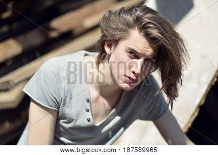 Portrait of young handsome man over wood boards, outdoor. Attractive trendy fashion 18 years old teen boy posing outside over construction waste