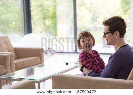 young mother and cute little girl enjoying their free time hugging on the sofa in their luxury home villa