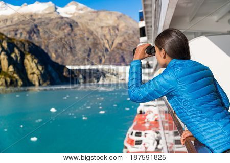 Tourist looking at Alaska Glacier Bay nature landscape using binoculars on cruise ship. Whale watching from boat. Luxury travel in USA.