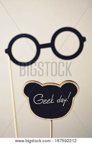 a pair of round-framed eyeglasses attached to a wooden handle and the text geek day written in a black signboard, on an off-white background