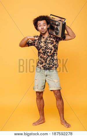 Picture of emotional african man standing with tape recorder isolated over yellow background. Looking at camera.
