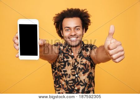 Close up portrait of a happy young afro american man showing blank screen mobile phone and giving thumbs up isolated over yellow background