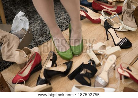 Hard choice. Close-up of young woman sitting in shoe store while different shoes laying near her
