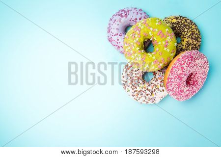 Donuts glazed with sprinkles on pastel blue background, close-up.