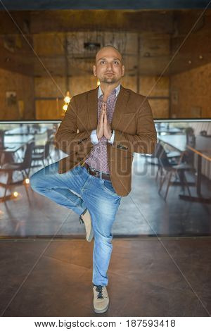 Handsome indian businessman weared in suit performing yoga or asana to relax, smiling lloking at camera.