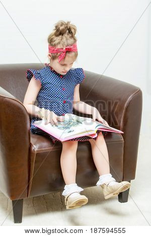Beautiful little girl preschooler sitting on a leather chair and reading a book.