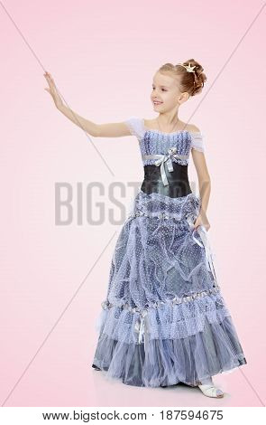 Slender little girl , with beautiful hair on his head, elegant long Princess dress.The girl stares at his palm like a mirror.Pale pink gradient background.