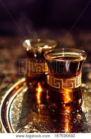 Two cups of steaming hot amber arabic tea on a golden ornate tray.